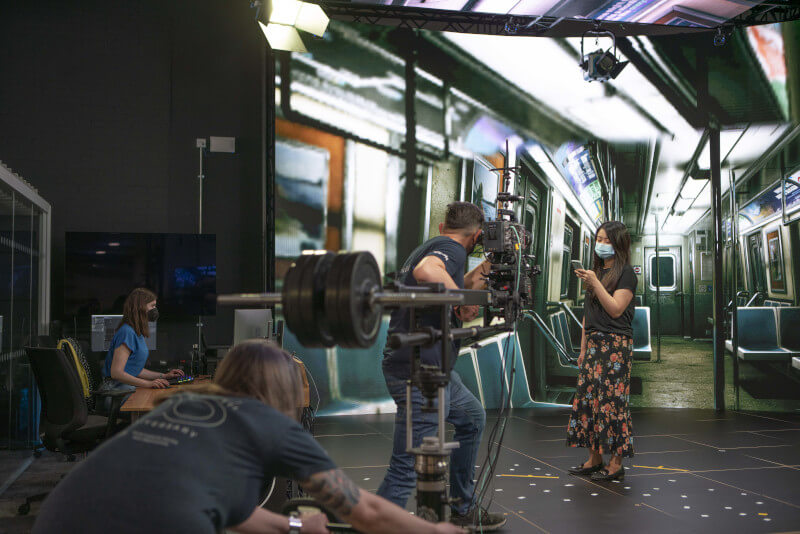 An actress films a scene with a underground train being projected on a screen behind her, being controlled by a technician in the corner